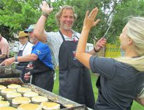 Rotarians Mark Lumley and Melissa Halloran high five in this file photo while cooking pancakes during the Rotary Club of Sarnia Mackinac race breakfast last year at Point Edward's Waterfront park. This year's breakfast is Saturday, 7 a.m. to 11 a.m. (File photo)