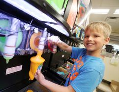 Seven-year-old Ella Holmes pours plenty of Slurpee into her cup on 7-Eleven Day in Selkirk July 11. (Brook Jones/Selkirk Journal/Postmedia Network)