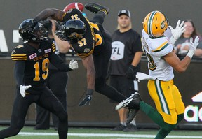 Hamilton Tiger-Cats defensive back Justin Rogers (left) watches teammate Richard Leonard leap to block a pass  intended for Edmonton wide receiver Brandon Zylstra. Hamilton lost again and the Eskimos remained undefeated.The Canadian Press