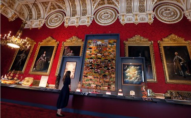 A woman looks towards a village scene of woven raw wool by Lentswe-la-Oodi Weavers, presented to Britain's Queen Elizabeth II by President Seretse Khama of Botswana in 1979, on display at Buckingham Palace in London, Thursday, July 20, 2017.(AP Photo/Kirsty Wigglesworth)