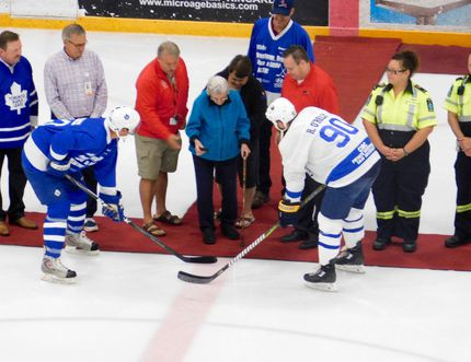 Boyd Devereaux (left) and Ryan O'Reilly (right) face off for the ceremonial opening puck drop, made by O'Reilly's grandmother.