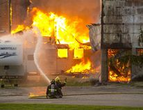 Firefighters pour water on a trailer, trying to prevent it from catching fire, as a horse barn burns to the ground at 2475 Gideon Dr. in Delaware Friday night. No horses were in the barn when the fire broke out. (DEREK RUTTAN, The London Free Press)