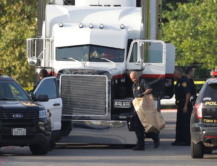 San Antonio police officers investigate the scene where eight people were found dead in a tractor-trailer loaded with at least 30 others outside a Walmart store in stifling summer heat in what police are calling a horrific human trafficking case in San Antonio, Texas, on Sunday, July 23, 2017. (Eric Gay/AP Photo)