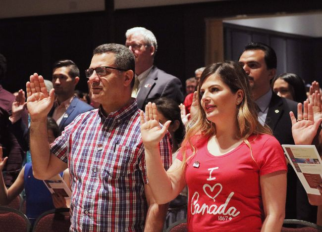 People take the citizenship oath at Pier 21 immigration centre in Halifax on Saturday, July 1, 2017. (Adina Bresge/The Canadian Press)
