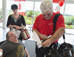 Dennis Laughlin of Brantford gets an autograph from former NHL player Marcel Dionne at the County of Brant's 150 community celebration at the Brant Sports Complex on Saturday. Brian Thompson/The Expositor