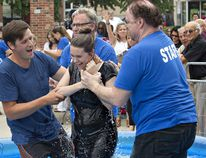 Accompanied by her friend Jason Mann (left), Hayden Riel of Norwich gets baptized by Pastor Brian Beattie during the 6th annual Baptism in the Square on Sunday in downtown Brantford. Brian Thompson/The Expositor