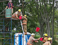 Firefighters from Norfolk County's Teeterville station work their way toward a first-place finish in the bucket brigade competition on Saturday at the Norfolk County Fire and Rescue firefighter pump competition in St. Williams. Brian Thompson/Postmedia Network