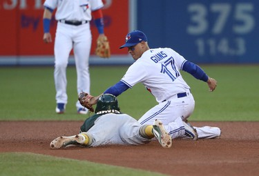 TORONTO, ON - JULY 25: Khris Davis #2 of the Oakland Athletics slides safely into second base with an RBI double in the fourth inning during MLB game action as Ryan Goins #17 of the Toronto Blue Jays applies the late tag at Rogers Centre on July 25, 2017 in Toronto, Canada. (Photo by Tom Szczerbowski/Getty Images)