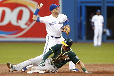 Toronto Blue Jays shortstop Troy Tulowitzki, top, turns a double play over Oakland Athletics Matt Chapman during third inning American League MLB baseball action in Toronto on Tuesday, July 25, 2017. THE CANADIAN PRESS/Mark Blinch ORG XMIT: MDB515 ORG XMIT: POS1707251909095145