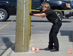 Det. Terri Jackson of London police forensics probes the scene of Tuesday's stabbing outside Goodwill Industries on Horton Street. Hashim Peters appeared in court on aggravated assault and weapons charges Wednesday. (MORRIS LAMONT, The London Free Press)