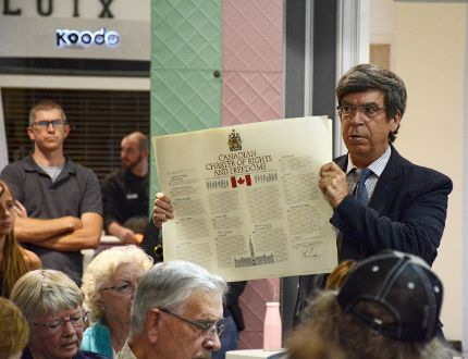 Norman Lee, a local lawyer, holds a copy of the Canadian Charter of Rights and Freedoms at MP Gord Brown's public meeting on the federal government's decision to award Omar Khadr with an apparent $10.5 million Tuesday night. (Sabrina Bedford/The Recorder and Times)