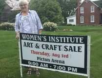 BRUCE BELL/THE INTELLIGENCER Prince Edward District Women's Institute president Evelyn Peck is pictured with one of the signs advertising the organization's 34th annual craft sale on Aug. 3, at the Picton Fairgrounds. The one-day event attracts thousands of visitors and raises approximately $20,000 annually for community initiatives, including accessible transportation in Prince Edward County.