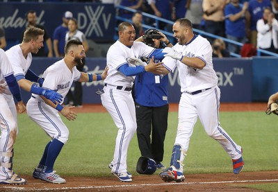 TORONTO, ON - JULY 26: Kendrys Morales #8 of the Toronto Blue Jays is congratulated by teammates after hitting a game-winning solo home run in the ninth inning during MLB game action against the Oakland Athletics at Rogers Centre on July 26, 2017 in Toronto, Canada. (Photo by Tom Szczerbowski/Getty Images)