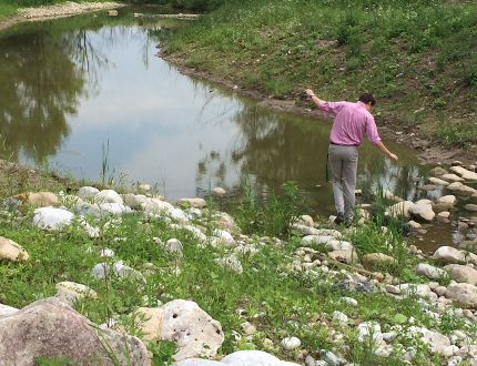 Zachary Cox, a summer student with the County of Oxford, takes a walk along a new river course that is part of the rehabilitation of Hodges Pond. (HEATHER RIVERS, Sentinel-Review)