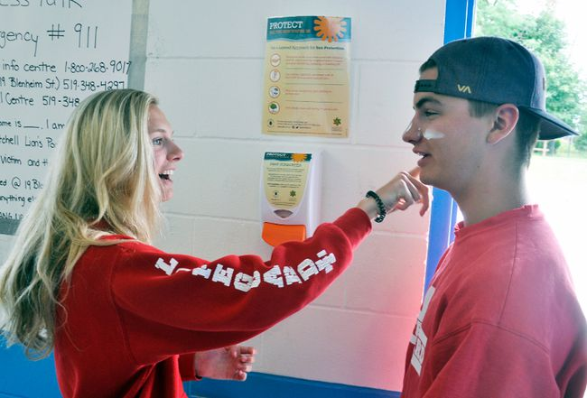Nicki Van Bakel (left), a lifeguard at the West Perth Lion's Pool, applies free sunscreen from relatively new dispensers at the pool to the face of lifeguard Thomas Rowland. The dispensers are used by swimmers, although lifeguard staff admit most users believe it's hand sanitizer. ANDY BADER/MITCHELL ADVOCATE