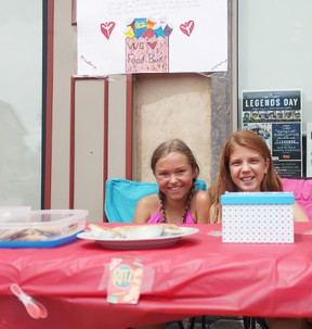 From the left, Bailey Stackhouse, 11, and Morgan Marks, 11 from Seaforth set up a lemonade stand and sold baked goods on Main Street last Friday. All the funds were donated to the Seaforth and District Foodbank. (Shaun Gregory/Huron Expositor)