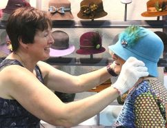 Bruce Bell photographs/The Intelligencer Picton's Elizabeth Lythgoe of Class Act Hats gives Shirley McGowan a hand trying on a new hat at the annual Prince Edward County Women's Institute Arts and Craft Sale at the Picton Fairgrounds on Thursday.