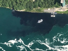 In this July 29, 2017 photo provided by Rainbow Air INC., black-coloured wastewater treatment discharge is released into water below Niagara Falls, in Niagara Falls, N.Y. (Patrick J. Proctor/Rainbow Air INC. via AP)