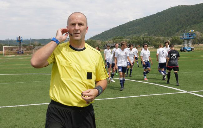In this July 11, 2017, still image from video, MLS referee Silviu Petrescu tests an earpiece and mic used to communicate with a video assistant referee during a video replay scrimmage organized in a community park, in Park City, Utah. Games were staged as part of the final training camp to gauge MLS referees' competence in and comfort with video replay. (AP Photo/Rick Bowmer)