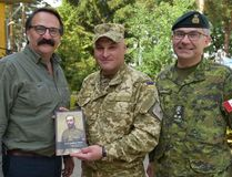 """Presenting Col. Igor Slisarchuk with a copy of """"A Canadian Hero"""" at IPSC, Yavoriv, Ukraine, on July 15. Lt.-Gen. Paul Wynnyk is at right."""
