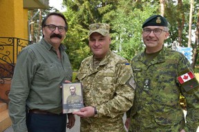 "Presenting Col. Igor Slisarchuk with a copy of ""A Canadian Hero"" at IPSC, Yavoriv, Ukraine, on July 15. Lt.-Gen. Paul Wynnyk is at right."
