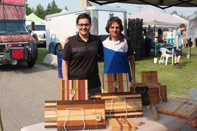 Graham Flaig, left and Liam Barrell from Airdrie Woodworks show off their work at the Airdrie Farmers Market on July 19, 2017. The teenagers started up their company last fall and are found at local farmers markets.