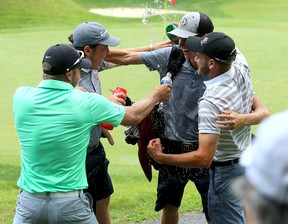 Calvin Ross, second from right, of Fredericton, New Brunswick gets a water shower from friends at the Cataraqui Golf and Country Club in Kingston on Thursday after winning the Canadian Junior Boys Golf Championship. (Ian MacAlpine/The Whig-Standard)