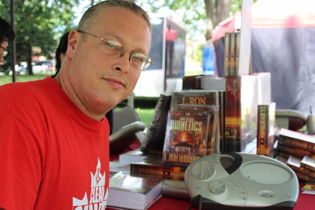 Travis Desmeules displays an e-meter at the Dianetics  booth run by Scientologists from Cambridge at London's Ribfest. (CHARLIE PINKERTON/The London Free Press)