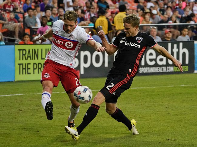 Toronto FC midfielder Nicolas Hasler shoots the ball past D.C. United defender Taylor Kemp during Saturday's game. (AP)