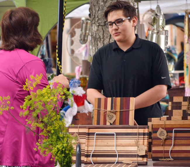 Fifteen year-old Graham Flaig discusses the work he and Liam Barrell, co-owners of Airdrie Woodworks, put into their home decor pieces for sale at Cochrane's Saturday Farmers' Market.