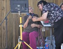 Virginia Broudy, right, helps an elder get set up at the mic during the karaoke fundraiser Broudy organized to help out a cancer patient.