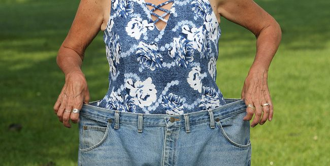 Colleen B, of Kingston, a member of Food Addicts in Recovery Anonymous, with a pair of jeans borrowed from the Phase 2 store the equivalent size of a woman's size 24 at Macdonald Park in Kingston on Thursday August 10 2017. She now a size 10. Ian MacAlpine /The Whig-Standard/Postmedia Network