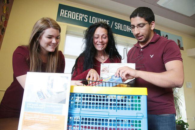 Giving the Basics organizers Sarah Lemieux, left, and Imran Bagha, along with Danielle Bray, drop-in co-ordinator at the Corner Clinic, sort through some of the donated items at the main branch of the Sudbury Public Library on Thursday. (Gino Donato/Sudbury Star)