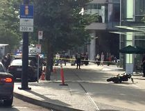 A motorcycle is on the ground in front of a shattered out glass window at the back of the Shaw tower. Cheryl Chan/Postmedia Network