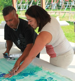 Aamjiwnaang artist John Williams helps Elizabeth Cronk place her paint-splattered left hand on his recently commenced mural, Destined For Greatness, on August 8th. CARL HNATYSHYN/SARNIA THIS WEEK CARL HNATYSHYN/SARNIA THIS WEEK