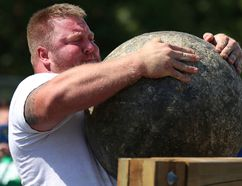 Tim Miller/The Intelligencer Ben Ruckstuhl heaves a 410 lb. Atlas stone over a bar during the Quinte Ribfest Strongman Challenge in Trenton's Centennial Park on Saturday in Quinte West.