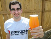 Justin Belanger hoists a glass of the Storm Stayed Brewing Company's lager. (MORRIS LAMONT, The London Free Press)