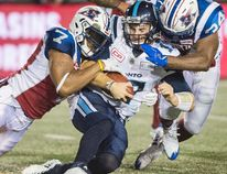 Toronto Argonauts quarterback Cody Fajardo is tackled by Montreal Alouettes' John Bowman and Kyries Hebert during CFL action in Montreal on Aug. 11, 2017. (THE CANADIAN PRESS/Graham Hughes)