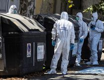 Italian police officers and forensic experts inspect a trash bin in which were found parts of human body in Rome, Wednesday, Aug. 16, 2017. Police in Rome say they are investigating a suspected murder after a pair of hacked-off legs, apparently of a woman, was found in a trash bin on an upscale street in the Italian capital, and a head and torso found in trash elsewhere. Police officials say they were questioning the brother of the victim Wednesday. (Angelo Carconi/ANSA via AP)