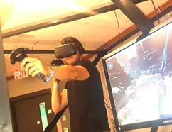 District Beta co-owner Travis Kelly demonstrates the virtual reality technology in one of the gaming booths which will be fully available after the site's opening on Sept. 1. (Jeremiah Rodriguez/The Observer)