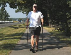 PAUL KRAJEWSKI HIGH RIVER TIMES/POSTMEDIA NETWORK. John Draper walks along the Happy Trails next to 12 Avenue SW in High River, Alta., with Nordic walking poles, designed to support his upper body and deliver a full-body workout, on Aug. 16, 2017.