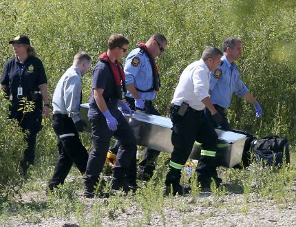 Police recover a body from the Red River