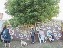 People add their own touches to the community mural at the On the Wall street art festival in August 2014. This year's event starts Monday. (Whig-Standard file photo)