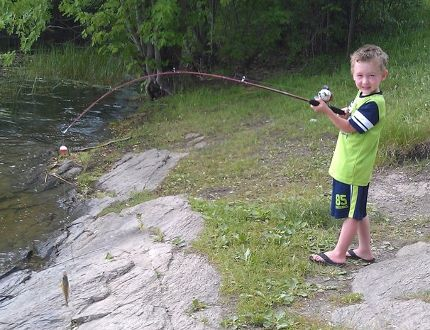 """Ethan Broome proudly displays his catch of the day. """"Green-time"""" has been shown to be beneficial to both children and adults."""