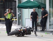 "A police officer photographs a motorcycle after a female stunt driver working on the movie ""Deadpool 2"" died after a crash on set, in Vancouver, B.C., on Monday August 14, 2017. THE CANADIAN PRESS/Darryl Dyck"