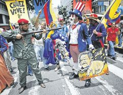 """Government supporters perform a parody involving a Venezuelan militia up against Uncle Sam, a personification of the U.S government, during an anti-imperialist march in Caracas Monday to denounce U.S. President Donald Trump's talk of a """"military option"""" for resolving the country's political crisis. (Ariana Cubillos/Associated Press)"""
