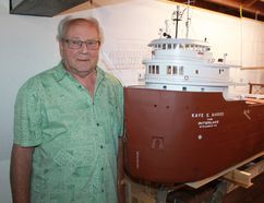Don Eastman stands beside a 13-foot model of the Great Lakes freighter the Kaye E. Barker in his workshop. The actual Barker was built in 1951 in Toledo and eventually purchased by the Ford Motor Company. Eastman has discovered that Henry Ford II sometimes entertained clients in a party room. CARL HNATYSHYN/SARNIA THIS WEEK