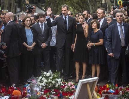 Spain's King Felipe and Queen Letizia wave to the crowd after paying respects at a memorial tribute of flowers, messages and candles to the van attack victims at Las Ramblas promenade, Barcelona, Spain, Saturday, Aug. 19, 2017. (Santi Palacios/AP Photo)