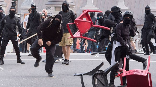 A demonstrator throws a chair during an anti-racism demonstration, in Quebec City on Sunday, Aug. 20, 2017. THE CANADIAN PRESS/Jacques Boissinot
