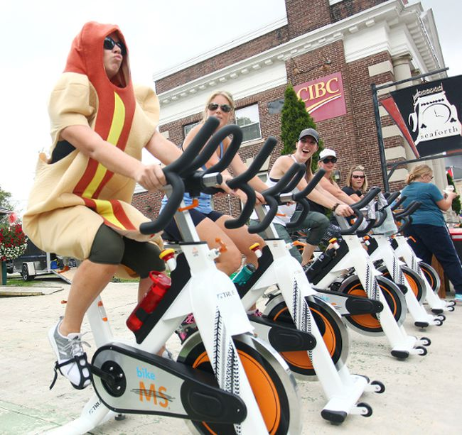 In the middle, Mandi Layton laughs as vice chair of the Seaforth BIA, Melody Hodgson makes some funny faces while working out in a hot dog suit last Friday in Seaforth. (Shaun Gregory/Huron Expositor)